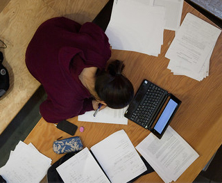 Student studying with computers and papers. MIT News photo all rights reserved.